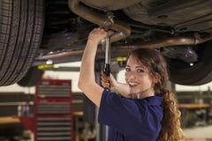工作在汽车下的女性汽车机械师画象  图库摄影