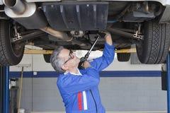 工作在汽车下的汽车修理师使用活动扳手 免版税图库摄影