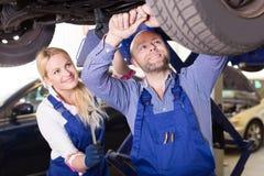 工作在汽车修理店的技工和助理 库存图片