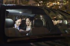 工作在汽车后面的两名女实业家 库存照片