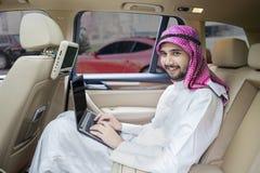 工作在汽车和微笑的阿拉伯人 免版税库存图片
