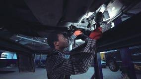 工作在汽车的下面的非洲技工 免版税库存图片
