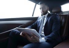 工作在汽车的后座和使用片剂的商人 免版税库存图片
