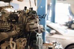 工作在汽车的技工,修理引擎 车库汽车服务 发动机阀汽车维护 在活塞的储蓄 免版税库存图片