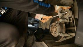 工作在汽车维修车间国内车库的闸的汽车机械师 影视素材