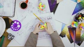 工作在汽车设计剪影和使用与5x5 Rubiks立方体的顶视图工程师 股票视频