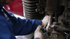 工作在汽车` s前面盘式制动器的汽车机械师 场面 人改变在汽车的闸在车库 影视素材
