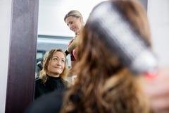 工作在沙龙的客户的头发的美发师 库存图片