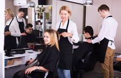 工作在沙龙的成熟美发师 免版税图库摄影