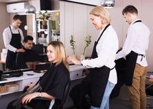 工作在沙龙的成熟美发师 免版税库存照片