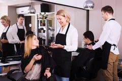 工作在沙龙的成熟美发师 库存照片