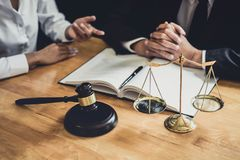 工作在法庭的男性律师或顾问开与客户的会谈是与不动产,法律合同纸的咨询  图库摄影