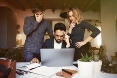 工作在流动便携式计算机上的现代演播室的三个年轻工友 水平,被弄脏的背景 视觉效果 图库摄影