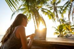 工作在海的女孩自由职业者在与计算机的日落 库存图片