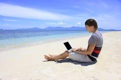 工作在海滩的一台膝上型计算机的商人与天蓝色的海和白色沙子 图库摄影