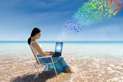 工作在海滩的少妇 免版税库存图片