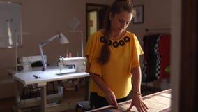 工作在演播室的时装设计师妇女 画衣裳的白种人女性裁缝布局在布料使用白垩 影视素材