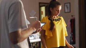 工作在演播室的时装设计师妇女 画衣裳的白种人女性裁缝布局在布料使用白垩 股票视频