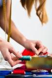工作在演播室的时装设计师或裁缝 库存图片
