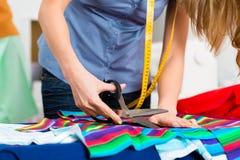 工作在演播室的时装设计师或裁缝 免版税库存图片