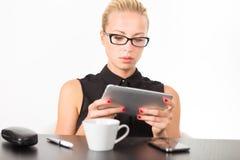 工作在片剂个人计算机的女商人 库存图片