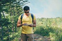 工作在片剂个人计算机的远足者人在夏天森林里 免版税库存照片