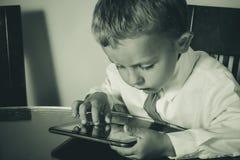 工作在片剂的企业男孩 免版税库存图片