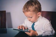 工作在片剂的企业男孩 免版税库存照片