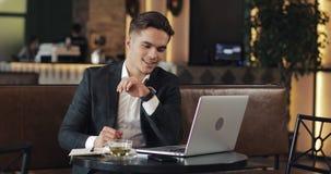 工作在现代办公室或共同工作和使用巧妙的手表的年轻商人 自由职业者谈话与smartwatch和 股票视频