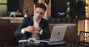 工作在现代办公室或共同工作和使用巧妙的手表的年轻商人 自由职业者谈话与smartwatch和 影视素材