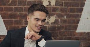 工作在现代办公室或共同工作和使用巧妙的手表的年轻商人 自由职业者谈话与smartwatch 4K 股票录像