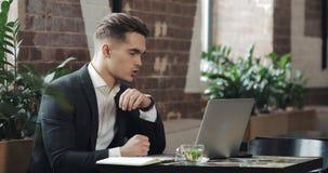 工作在现代办公室或共同工作和使用巧妙的手表的年轻商人 自由职业者谈话与smartwatch 4K 影视素材