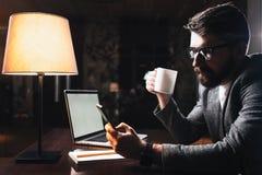 工作在现代办公室的年轻商人在晚上 免版税库存图片