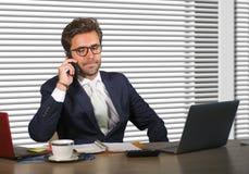 工作在现代办公室的年轻愉快和繁忙的商人生活方式公司公司画象谈话在手机由风 免版税库存图片