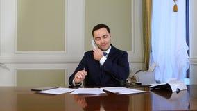 工作在现代办公室的年轻确信的成功的商人分析事务由电话交谈 免版税库存照片