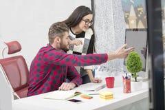 工作在现代办公室的年轻设计师夫妇,谈论两个的工友乐趣射出在膝上型计算机, 免版税图库摄影