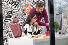 工作在现代办公室的年轻设计师夫妇,谈论两个的工友乐趣射出在膝上型计算机, 图库摄影