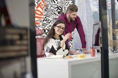 工作在现代办公室的年轻设计师夫妇,谈论两个的工友乐趣射出在膝上型计算机, 库存图片
