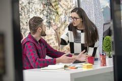 工作在现代办公室的年轻设计师夫妇,谈论两个的工友乐趣射出在膝上型计算机, 免版税库存图片