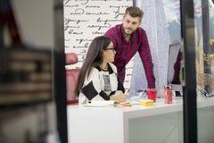 工作在现代办公室的年轻设计师夫妇,谈论两个的工友乐趣射出在膝上型计算机, 库存照片