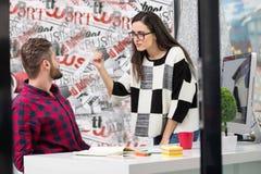 工作在现代办公室的年轻设计师夫妇,谈论两个的工友乐趣射出在膝上型计算机, 免版税库存照片