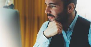 工作在现代办公室的有胡子的年轻商人在晚上 顾问人想法的看在显示器计算机 键入o的经理 库存图片