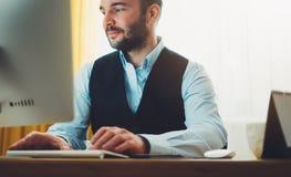工作在现代办公室的有胡子的年轻商人在晚上 顾问人想法的看在显示器计算机 键入o的经理 免版税图库摄影