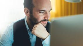 工作在现代办公室的有胡子的年轻商人在晚上 顾问人想法的看在显示器计算机 键入o的经理 免版税库存照片