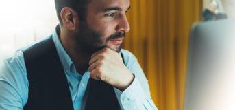 工作在现代办公室的有胡子的年轻商人在晚上 顾问人想法的看在显示器计算机 键入o的经理 库存照片