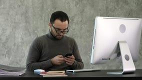 工作在现代办公室的有胡子的年轻商人 看在他的智能手机和键入某事的人 库存图片