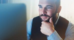 工作在现代办公室的有胡子的年轻商人 顾问人想法的看在显示器计算机 键入在keyboar的经理