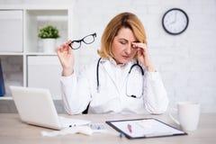工作在现代办公室的被注重的或疲乏的成熟女性医生 免版税库存图片