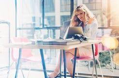 工作在现代办公室顶楼的可爱的白肤金发的妇女 使用在工作场所的工友电子触板计算机 免版税库存照片
