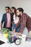 工作在现代办公室的三个同事队  免版税库存图片